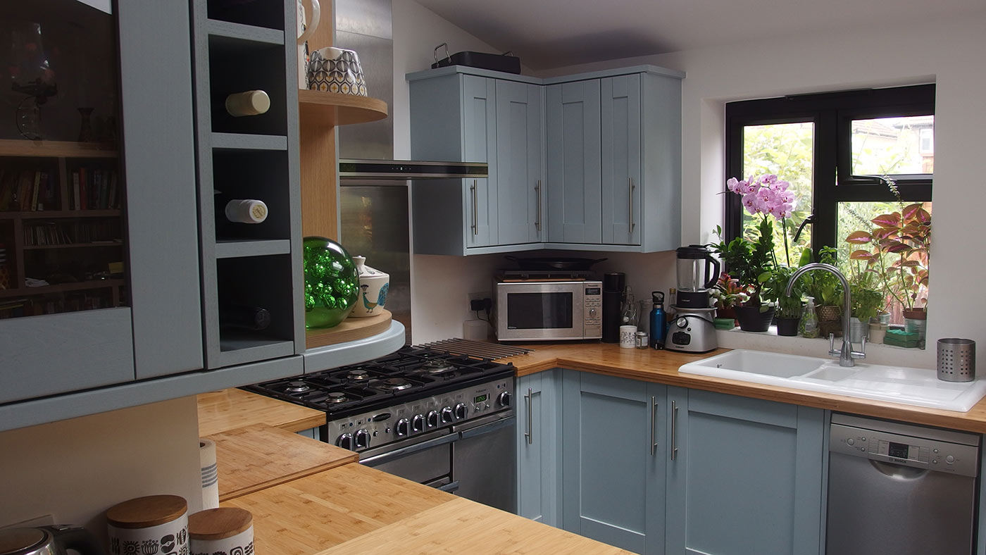 Kitchen with bamboo worktop and blue cupboards.