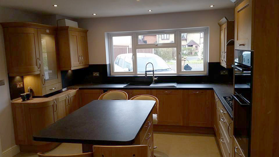 Kitchen with black worktop and wooden cupboards.